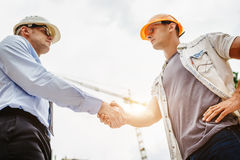 Architect engineer shaking hands other hand at construction site. Business teamwork, cooperation, success collaboratio. N concept royalty free stock images