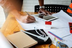 Architect or engineer using pen working on blueprint stock photography