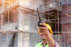 Architect engineer using walkie-talkie talking with assistant. While working front of building site Royalty Free Stock Photo