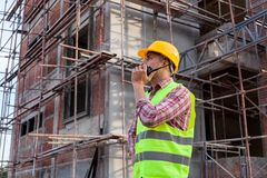 Architect engineer using walkie-talkie talking with assistant wh. Ile working front of building site Stock Photo