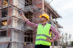 Architect engineer using walkie-talkie talking with assistant wh. Ile working front of building site Royalty Free Stock Photography
