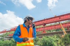 Architect or Engineer, wearing white Hardhat and safety vest, us. E Radio Communication to supervise Motorway Project Development as Infrastructure Construction royalty free stock images