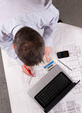 Architect examines plans. Architect or engineer calculates and draws on blueprint. Focus on tabletop. Elevated view Royalty Free Stock Photography