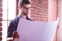 Architect examining blueprint. Royalty Free Stock Image