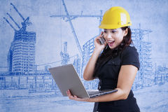 Architect excited looking at laptop on blueprint Royalty Free Stock Photography