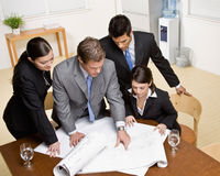 Architect explains blueprint to co-workers. Architect explains problem on blueprint to co-workers in conference room Royalty Free Stock Photography