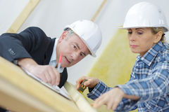 Architect and female worker examining blueprints Stock Image