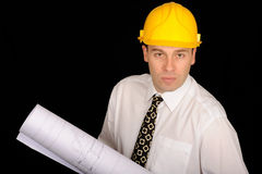 Architect with floor plans. A male architect holds a roll of floor plans as he looks into the camera, yellow hard hat on his head Stock Photo