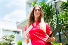 Architect with folding rule in front of house. Female Architect with folding rule and clipboard in front of house Royalty Free Stock Image