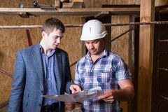 Architect and Foreman Inspecting Building Plans Stock Photo