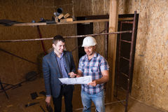 Architect and Foreman Inspecting Building Plans Royalty Free Stock Photo