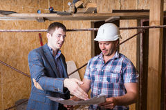 Architect and Foreman Inspecting Building Plans. Young Male Architect and Construction Worker Foreman Inspecting Building Plans Together Inside Unfinished Royalty Free Stock Photos