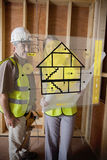 Architect and foreman standing behind house plan interface Stock Photo