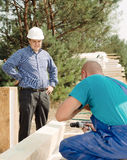 Architect or foreman watching a builder Royalty Free Stock Photos