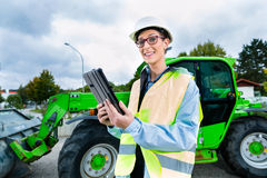 Architect in front of excavator using pad or tablet Royalty Free Stock Photos