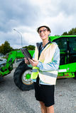 Architect in front of excavator using pad or tablet Royalty Free Stock Image