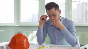 Architect gets tired at the office. Attractive male architect getting tired at the office. Young building designer massaging his eyes. Handsome construction