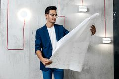 Architect in glasses dressed in blue checkered jacket and jeans works with blueprints on the background of the concrete stock photos
