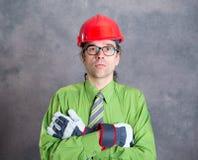 Architect in groen overhemd met rode helm en gekruiste wapens royalty-vrije stock afbeeldingen