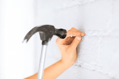 Architect hammering nail in wall Stock Images