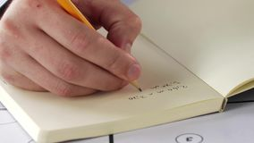 Architect hand with blueprint writing to notebook stock footage