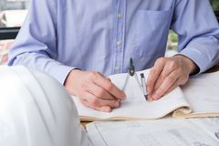 Architect hand holding drawing compass working on construction p Stock Photos