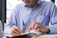 Architect hand holding drawing compass working on construction p Stock Images