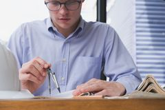 Architect hand holding drawing compass working on construction p Royalty Free Stock Image