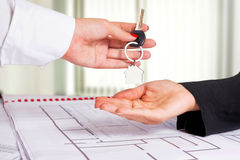 Architect hand presenting house key to a client. Stock Images