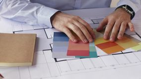Architect hands with blueprint and color palettes stock footage