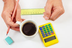 Architect hands holding a cup of coffee and pencil Royalty Free Stock Images