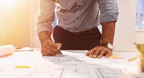 Architect hands working on blueprint. Busy architect checking the details of a blueprint. Casual man working on an architecture model with pencil at office stock images