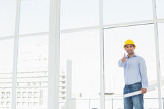Architect in hard hat with blueprint gesturing thumbs up in office. Portrait of a smiling architect in yellow hard hat with blueprint gesturing thumbs up in a Royalty Free Stock Photos
