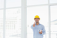 Architect in hard hat with blueprint gesturing thumbs up in office. Portrait of a smiling architect in yellow hard hat with blueprint gesturing thumbs up in a Stock Image