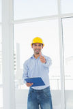 Architect in hard hat with clipboard gesturing thumbs up in office Royalty Free Stock Image