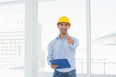 Architect in hard hat with clipboard gesturing thumbs up in office Royalty Free Stock Photos