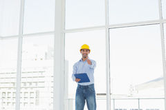 Architect in hard hat with clipboard gesturing thumbs up in office Stock Photography
