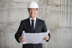 Architect in hard hat holding blueprint and smiling at camera Royalty Free Stock Images