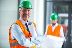 Architect in hard hat standing with blueprint in office corridor. Portrait of architect in hard hat standing with blueprint in office corridor Stock Photography