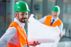 Architect in hard hat standing with blueprint in office corridor. Portrait of architect in hard hat standing with blueprint in office corridor Stock Photos