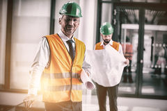 Architect in hard hat standing with blueprint in office corridor. Portrait of architect in hard hat standing with blueprint in office corridor Stock Images