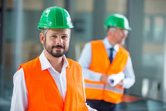 Architect in hard hat standing in office corridor Stock Image