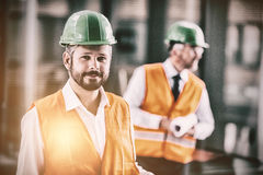 Architect in hard hat standing in office corridor. Portrait of architect in hard hat standing in office corridor Royalty Free Stock Images