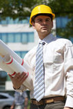 Architect in hardhat holding blueprint at construction site Stock Images