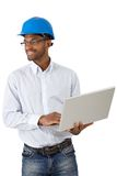 Architect in hardhat with laptop. Smiling architect in hardhat working with laptop computer, cutout on white Stock Image