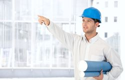Architect in hardhat pointing. Architect wearing hardhat holding work plan standing in office, pointing Royalty Free Stock Image