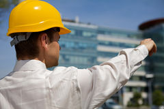 Architect in hardhat pointing at construction site Royalty Free Stock Images
