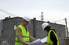 Architect with his assistant. Photo of architect and his assistant on building site stock photo