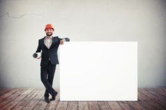 Architect holding blank horizontal white banner. Place for text. Royalty Free Stock Photo