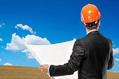 Architect holding a blueprint. A view of an architect holding a blueprint with a green meadow in the background Stock Photo